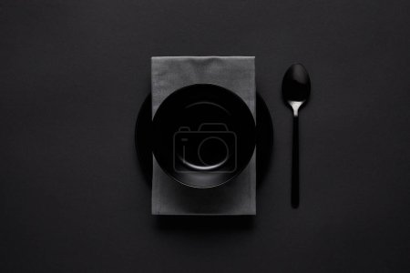 top view of black bowl, spoon, kitchen towel and plate on black table, minimalistic concept