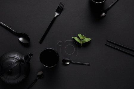 Photo pour Vue de dessus de théière noire, baguettes, diverses cuillères, fourchette, tasse et feuilles de menthe sur table noire - image libre de droit