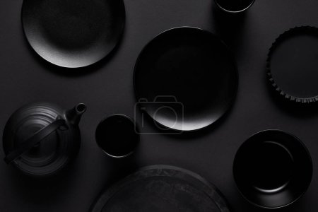 top view of black teapot, plates, bowl, cups, tray and baking dish on black table