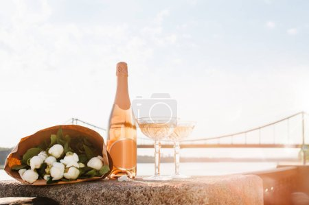 close-up view of beautiful bouquet of flowers, two glasses and bottle of champagne near river at sunset