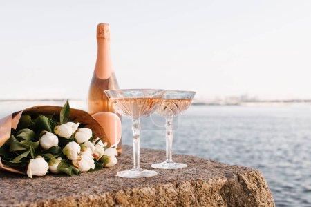Photo pour Vue rapprochée de deux verres, bouteille de champagne et beau bouquet de fleurs sur remblai au bord de la rivière - image libre de droit