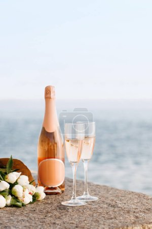 close-up view of beautiful bouquet of flowers and champagne in glasses and bottle on embankment