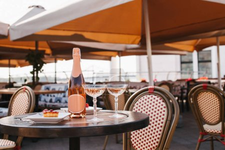 bottle of champagne, two glasses and delicious desserts on table in outdoor cafe