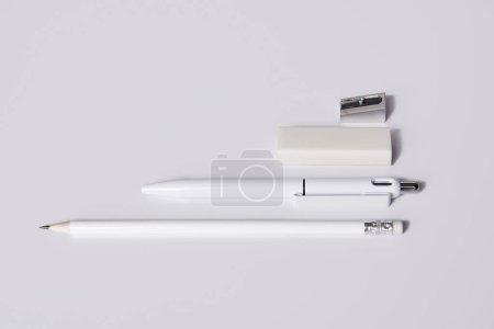 Nahaufnahme von weißem Stift mit Bleistift, Radiergummi und Spitzer reihenweise auf weißer Oberfläche für Attrappen angeordnet