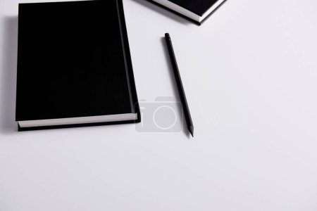 close-up shot of black hard cover notebooks with pencil on white surface