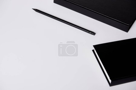 Photo for Close-up shot of black hard cover notebooks with pencil on white tabletop - Royalty Free Image