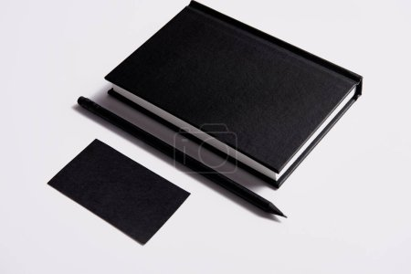isometric view of black notebook with pencil and business card on white tabletop for mockup