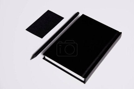 isometric view of black notebook with pencil and business card on white surface for mockup