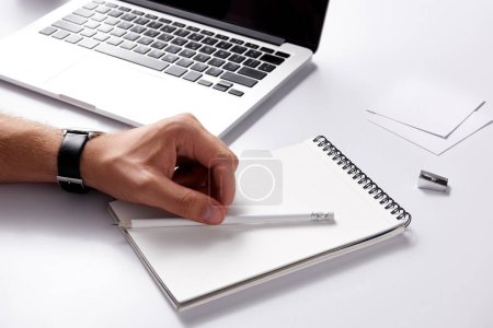 cropped shot of man with notebook and pencil lying at workplace on white surface