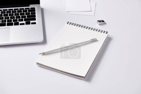 close-up shot of notebook and pencil at workplace on white surface