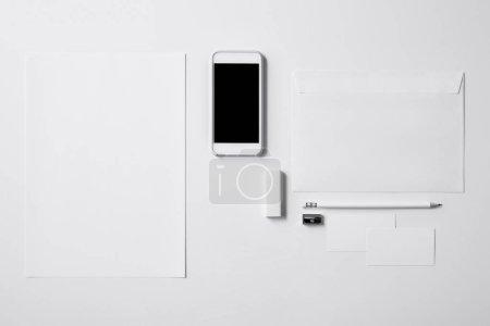 Photo pour Vue du haut du smartphone avec écran vierge et fournitures de bureau sur table blanche pour la maquette - image libre de droit