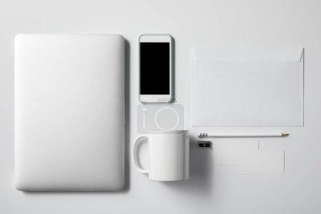 Photo pour Vue de dessus de l'ordinateur portable avec smartphone, tasse et fournitures de bureau sur la table blanche pour la maquette - image libre de droit