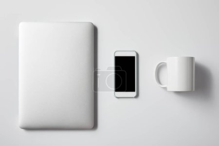 top view of laptop with smartphone and cup on white tabletop for mockup