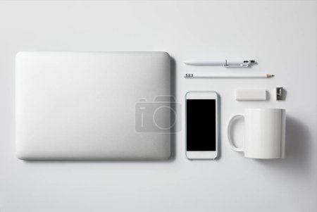 top view of laptop with smartphone and office supplies on white tabletop for mockup