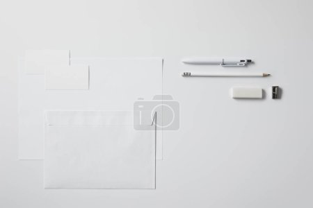 top view of various paper objects and office supplies on white surface for mockup