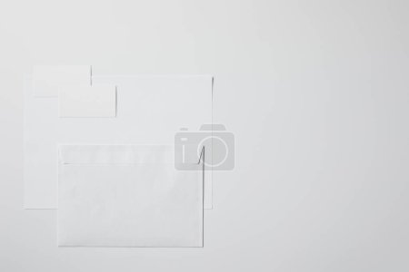 top view of blank paper with envelope and business cards on white surface for mockup