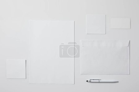 top view of various paper objects with pen on white surface for mockup