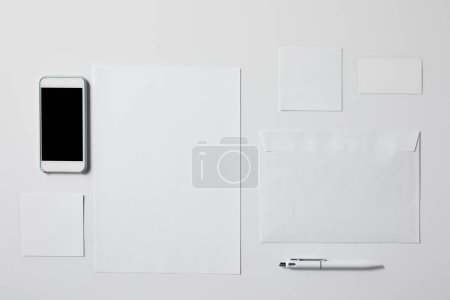 top view of smartphone with various blank papers and pen on white tabletop for mockup