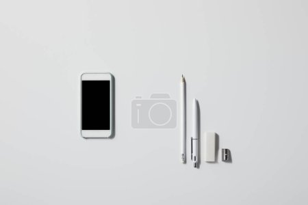 top view of smartphone with various supplies in row on white tabletop for mockup