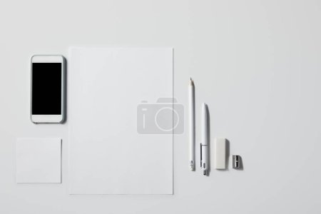 top view of smartphone with various supplies on white tabletop for mockup