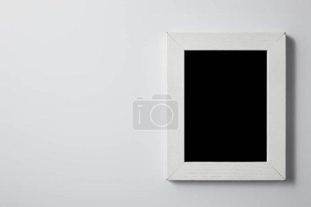 vista superior de pizarra en blanco con marco de madera blanco sobre superficie blanca para maqueta
