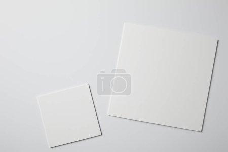 Photo pour Vue de dessus des papiers carrés sur la surface blanche - image libre de droit
