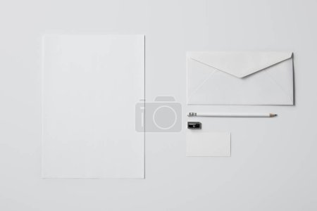 top view of business mockup with paper supplies and pencil on white surface for mockup