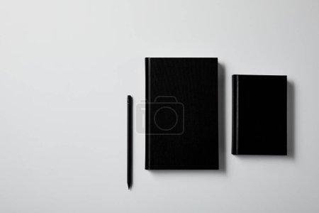 Photo pour Vue de dessus des cahiers noirs avec crayon sur la surface blanche pour la maquette - image libre de droit