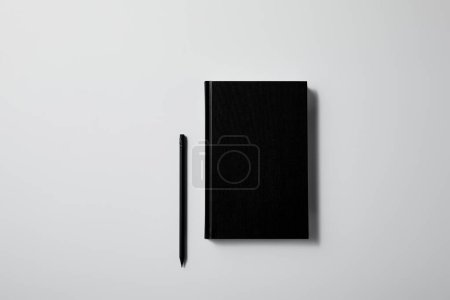top view of black notebook with pencil on white surface for mockup