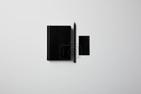 top view of black notebook with pencil and blank business card on white surface for mockup