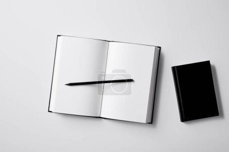 top view of black notebooks with pencil on white surface for mockup
