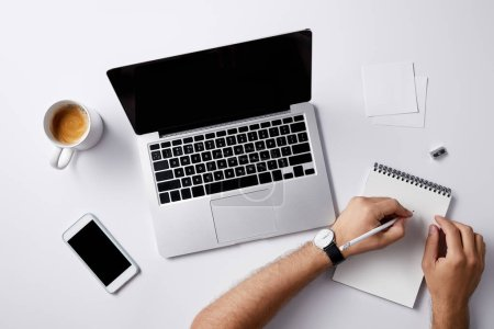 Photo for Cropped shot of man writing in notebook at workplace with gadgets and coffee cup on white surface for mockup - Royalty Free Image