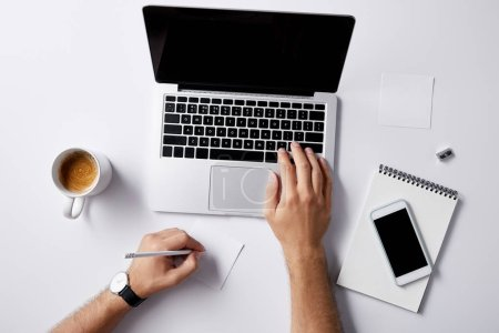 cropped shot of man working with laptop at workplace on white surface for mockup