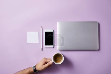 cropped shot of man folding coffee cup at workplace on pink surface for mockup