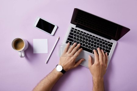 cropped shot of man using laptop at workplace on pink surface for mockup