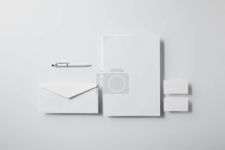 top view of layered envelope with pen, blank paper and business cards on white surface for mockup