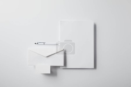 top view of layered envelope with pen, blank paper and business card on white surface for mockup