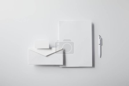 top view of arranged envelope with pen, blank paper and business card on white tabletop for mockup