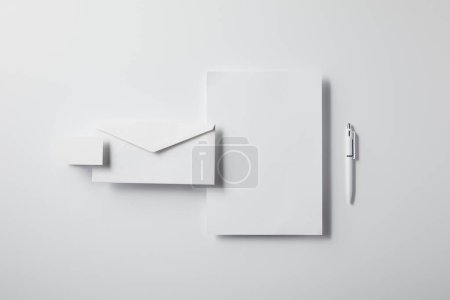top view of layered envelope with pen, blank paper and business card on white tabletop for mockup
