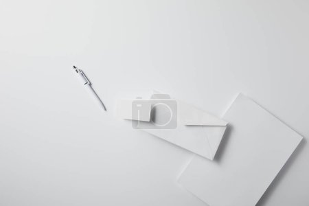 top view of arranged envelope with pen, blank paper and business card on white surface for mockup