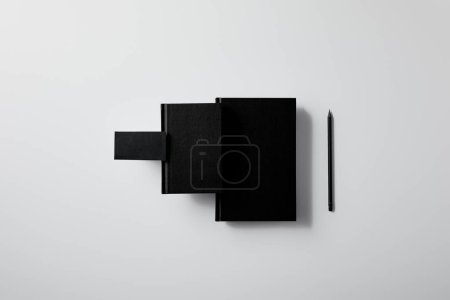 top view of black notebooks with business card and pencil in row on white surface for mockup