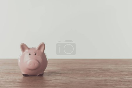 small pink piggy bank on wooden table, saving concept