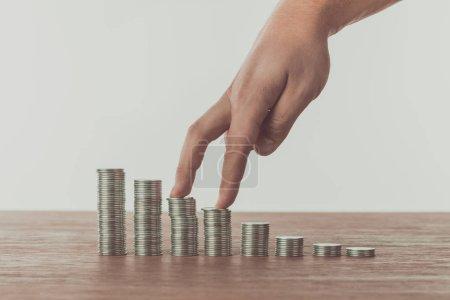 Cropped image d'homme marchant avec les doigts sur des piles de pièces sur la table, sauver le concept