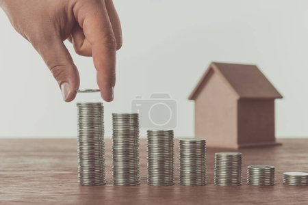 cropped image of man stacking coins near small house on table, saving concept