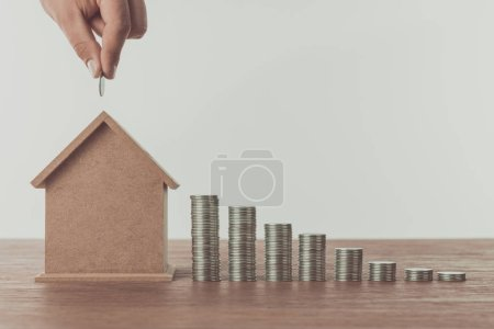 cropped image of man putting coin into small house on wooden table, saving concept