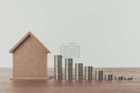 small wooden house and stacks of coins on wooden table, saving concept