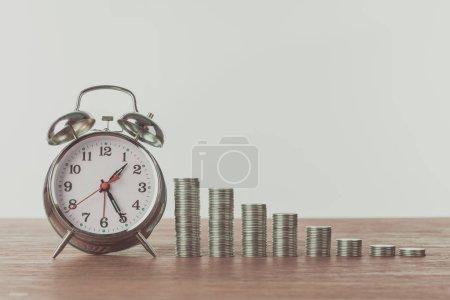 Photo pour Radio-réveil et piles de pièces de monnaie sur la table en bois, sauver le concept - image libre de droit