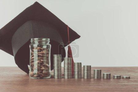 Foto de Pilas de monedas, tarro con monedas y el casquillo de la graduación en mesa de madera, concepto de ahorro - Imagen libre de derechos