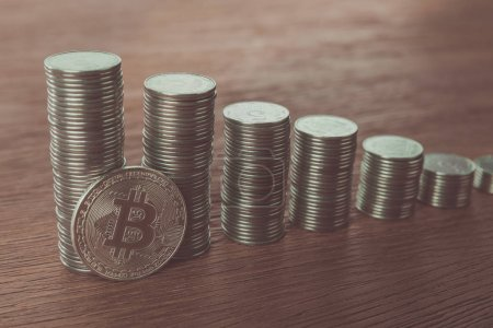bitcoin near stacks of coins on tabletop, saving concept