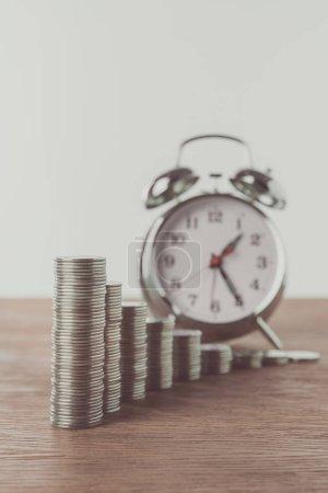 Photo pour Piles de pièces de monnaie et de réveil sur la table en bois, sauver le concept - image libre de droit